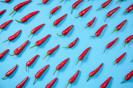 Hot red peppers randomly on blue background,flat lay design.