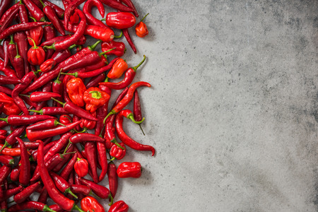 Red mixed peppers border background. Stock Photo