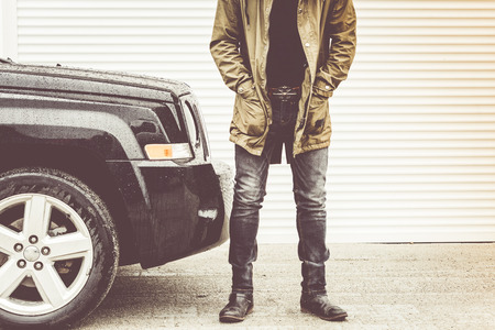 Hipster fashion jeasn and off road car in garage. Stock Photo