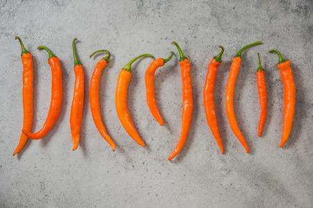 Orange peppers on stone slate.