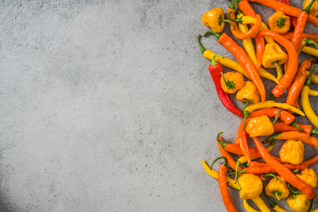 Orange and yellow peppers on stone slate