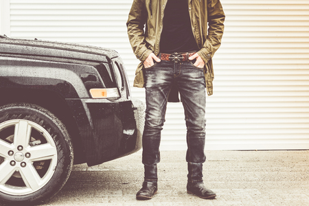 Fashion handsome man standing by 4x4 car agains garage door Stock Photo