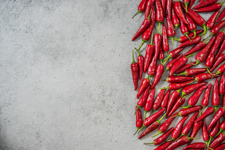 Hot red chili peppers border background.