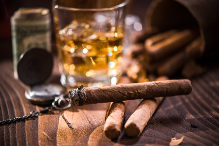 Glas with Whiskey over ice cubes and cuban cigar. Money and expensive watch in background Stock Photo