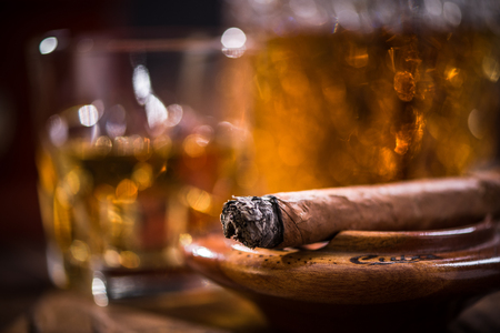 Cuban cigar smoking in wooden ashtray, carafe with Cognac in background