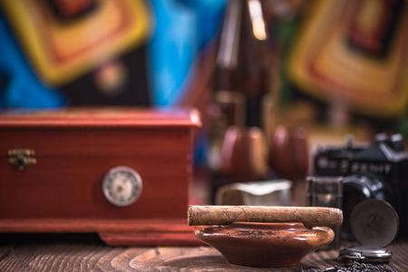 Wooden humidor, cigars and ashtray.