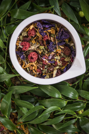 Aromatic colorful tea in pot over green leaves.
