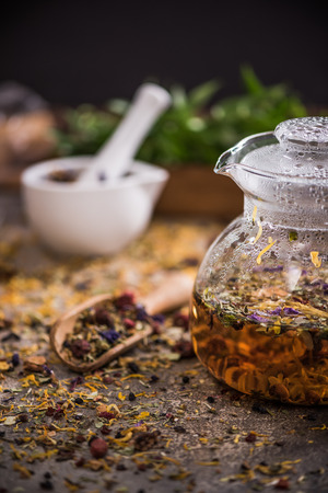 Hot aromatic herbal tea in glass kettle.