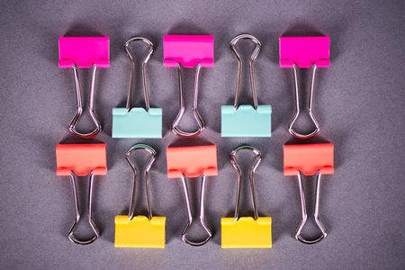 Vibrant pastel metal paperclips on grey background, office supplies Stock Photo