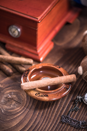 Cuban cigar in ashtray on wooden table, items related to travel to Cuba. Stock Photo
