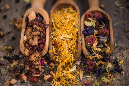 Assorted loose aromatic herbal tea on wooden spoons.