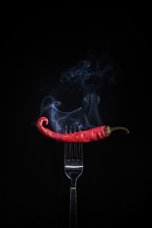 Smoking red hot chili on fork.
