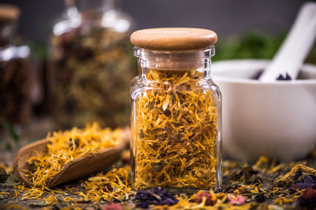 Tea with dried flowers and fruits in jar.