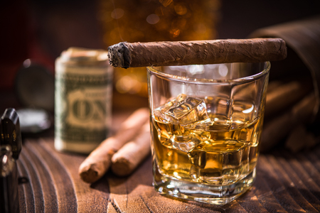 Glas with Whiskey over ice cubes and cuban cigar. Money and expensive watch in background Stock fotó