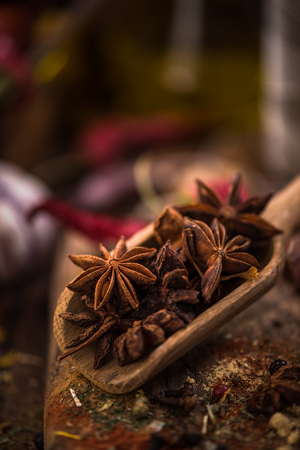 Whole anise stars on wooden spoon.
