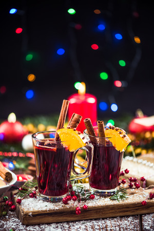 Serving festive hot mulled red wine. Christmas decorated table. Stock Photo
