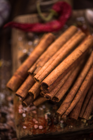 Whole cinnamon stocks on wooden boar. Spices concept.