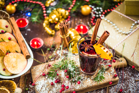 Red mulled hot wine in glass with spices.