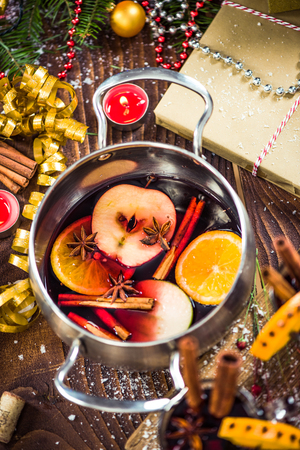 Spices and mulled wine in pot.