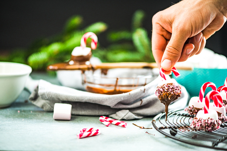 Dipping marshmallow in hot chocolatte. Creative Christmas sweets.