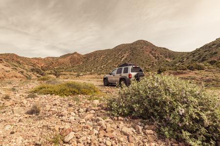 山でのキャンプでオフロード車。打たれたトラックを離れて未知の場所で道路の旅行。