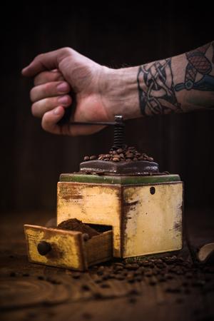 tattooed hand and coffee grinder,dark moody toned image Reklamní fotografie