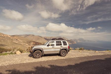 湖を望む高山の道路旅行車。打たれたトラックを離れて未知の場所で道路の旅行。