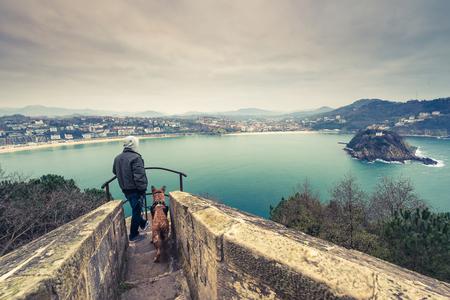 Man and german shepherd dog traveling together. Admiring view over San Sebastian in Spain. Фото со стока