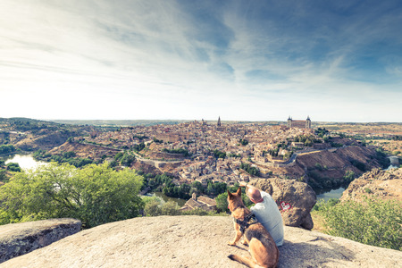 TRaveller man and dog watching Toledo cityscape from hill. Фото со стока