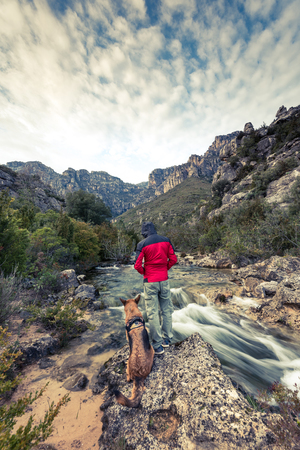 Wanderlust man and dog in wild mountains by the river.