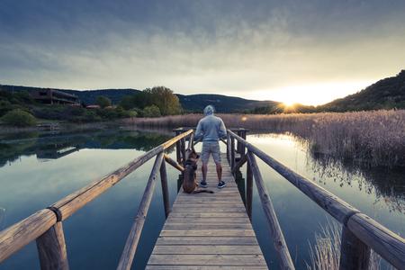 Sunrise at lake, copule travellers. Фото со стока