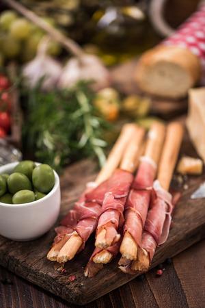 Bread sticks with prosciutto ham,italian tapa food.