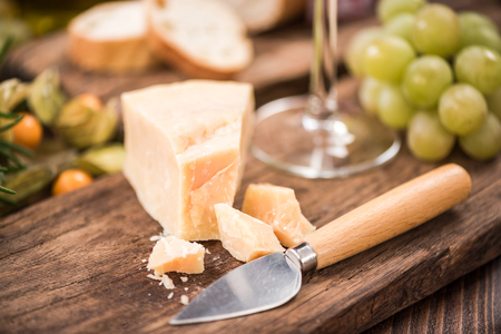 Piece of parmesan cheese with knife on board.