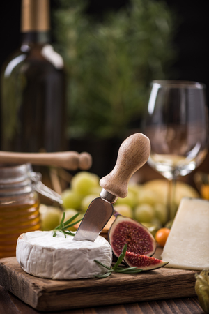 Camembert cheese on board with fig .