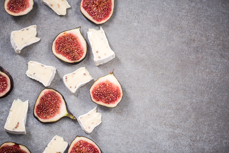 Camembert and fresh figs on stone slate, top view.