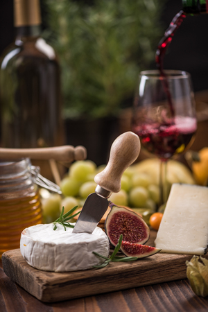 Pouring red wine into glass and serving with camembert.