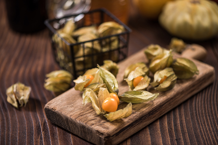Physalis fruits on wooden board.