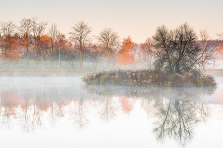 Trees at lake egde reflect in water with autumn colors, misty morning Banco de Imagens - 88647789