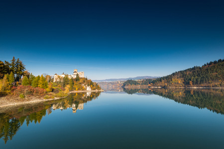 Panoramic image over lake with Nidzica castle at autumn.