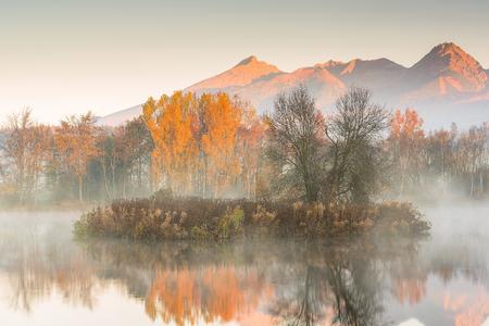 Sunrise light hits high mountains peaks in Tatra mountains.