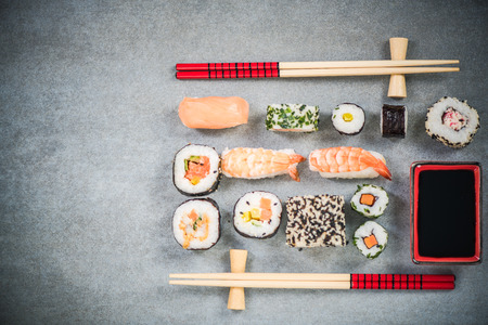 Sushi on stone or concrete slate with chopsticks. Фото со стока
