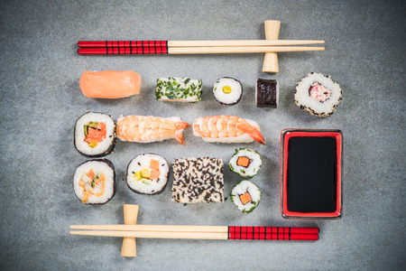 Sushi on stone or concrete slate with chopsticks. Stock Photo