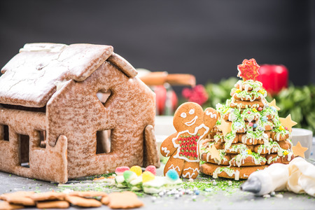 Making gingerbread house and sweet Christmas tree in creative artisan bakery