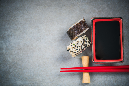 Chopsticks and soy sauce on stone concrete board. Stock Photo