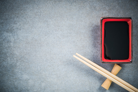 Chopsticks and soy sauce on stone concrete board. Stock Photo - 90015351
