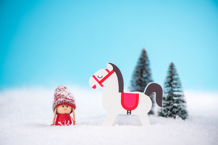 Little girl with rocking wooden horse on snow. Stock Photo