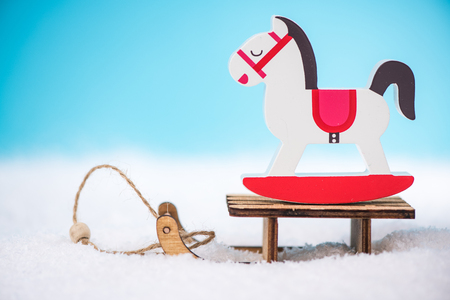 Wooden rocking horse on snow sledge.