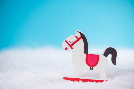 Vintage wooden rocking horse toy in snow,copy space Stock Photo