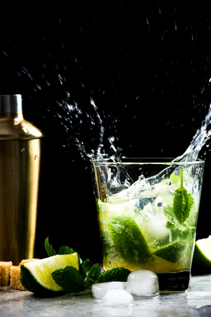 Dynamic high speed Mojito coctail splash on bar. Stock Photo