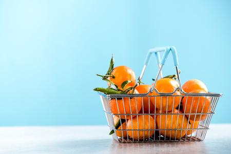 Shopping basket ful of oranges.